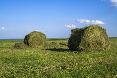 Straw bales on a field in the foreground.  Harvest of hay. Clouds in the sky. Agricultural farm. Hills with cultivated fields and. Straw bales on a field in the stock image