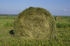 Straw bales on a field in the foreground.  Harvest of hay. Clouds in the sky. Agricultural farm. Hills with cultivated fields and. Straw bales on a field in the stock photo
