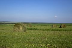Straw bales on a field in the foreground.  Harvest of hay. Clouds in the sky. Agricultural farm. Hills with cultivated fields and. Straw bales on a field in the stock photography