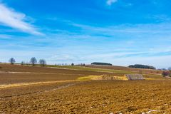 Straw bales and manure on the countryside field. Spring fields and preparation for agriculture. Typical czech countryside land, tr. Ees and blue sky Stock Photo