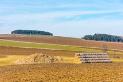 Straw bales and manure on the countryside field. Spring fields and preparation for agriculture. Typical czech countryside land, tr. Ees and blue sky Royalty Free Stock Images