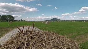 Straw bales on the meadow, white clouds in the sky in Hungary.  stock footage