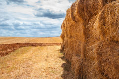 Straw bales over mown field, cloud cover Royalty Free Stock Photography