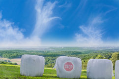 Straw bales with Stop icon. Three straw bales in white plastic film on a field. The average bale imprinted Stop stock images