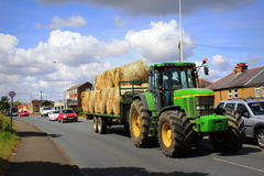 Straw bales tractor on countryside road UK Stock Photos