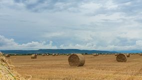 Straw bales under cloudy skies - time lapse stock footage