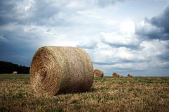 Straw bales under stormy clouds stock photo