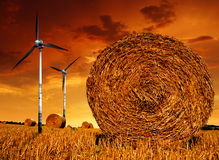 Straw bales with wind turbine. Straw bales on farmland with wind turbine in the sunset Stock Photos