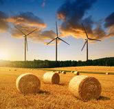 Straw bales with wind turbines Royalty Free Stock Image