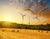 Straw bales with wind turbines on farmland Royalty Free Stock Images