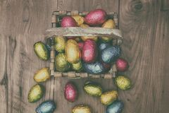 Straw basket filled with Easter chocolate eggs wrapped in colorful tinfoil. On top of a wooden table Stock Image