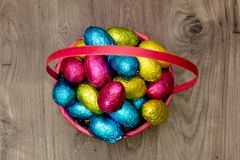 Straw basket filled with Easter chocolate eggs wrapped in colorful tinfoil royalty free stock photos