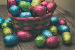 Straw basket filled with Easter chocolate eggs wrapped in colorful tinfoil Royalty Free Stock Images