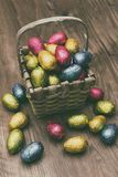 Straw basket filled with Easter chocolate eggs wrapped in colorful tinfoil stock photo
