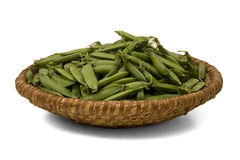 Straw basket with green peas. Straw basket with pods of green peas Stock Image