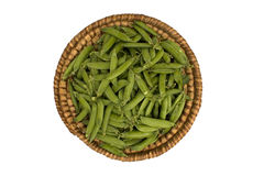 Straw basket with green peas. Straw basket with pods of green peas Royalty Free Stock Photo