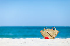 Straw beach bag on exotic white sand beach Stock Images