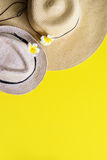 Straw Beach Pair Outfit Woman`s Men`s Hat Yellow. Straw Beach Pair Outfit Woman`s Men`s Hat with White Frangipani Top View Yellow Background Flat Lay Royalty Free Stock Photos