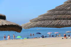 Straw beach parasol to shelter from the hot summer sun Royalty Free Stock Images
