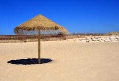 Straw beach sunshade, Deserted beach, Near Lisbon, Portugal. Stock Images