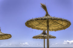 Straw beach umbrella against blue sky Stock Photo