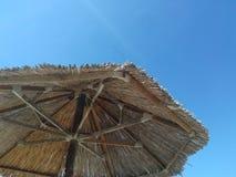 Beach umbrella and sky. Straw beach umbrella Stock Images