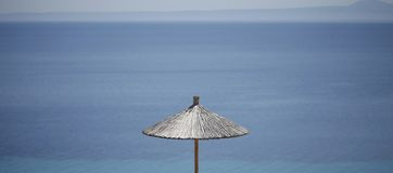 Straw beach umbrella with a blue sea on the background Stock Photo