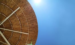 Straw beach umbrella close-up in front of blue bright sky. royalty free stock photography
