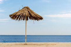 Straw beach umbrella on an empty seashore on a clear day royalty free stock image