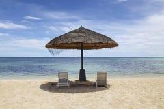 Straw Beach Umbrella mit weißen Strand-Stühlen auf Mikrostrand in Saipan stockbilder