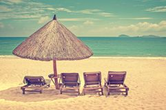 Straw beach umbrella and wooden reclining chairs on a perfect beach vintage process. Straw beach umbrella and wooden reclining chairs on a perfect beach, vintage Stock Photography