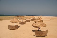 Straw beach umbrellas Stock Photos
