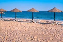 Straw beach umbrellas on ocean coast Stock Photo