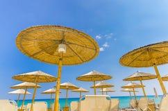 Straw beach umbrellas. And sandy beach Kalamaki at Zakynthos, Greece on blue colorful sky, view from below Stock Photo
