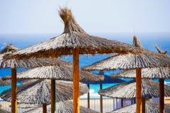 Straw beach umbrellas Stock Photos