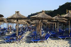 Straw beach umbrellas and sunbeds on the beach Stock Image