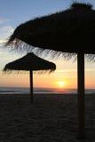 Straw beach umbrellas at Sunset Stock Photo