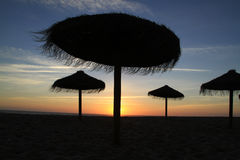 Straw beach umbrellas at Sunset Stock Images