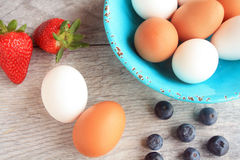 Straw berries and blue berries a  green bowl full of brown and white eggs Stock Photography