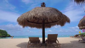 Straw big umbrella with two empty sunbeds at paradise beach on Bali, Indonesia. Perfect vacation stock video footage