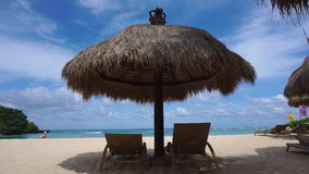 Straw big umbrella with two empty sunbeds at paradise beach on Bali. Indonesia. Perfect vacation stock video