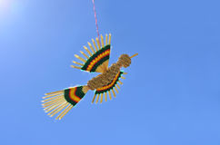 Straw bird flying on a thread against bright blue sky Royalty Free Stock Photo