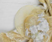 A straw bonnet and white and ivory silk flowers on a rustic wooden white washed background royalty free stock photo