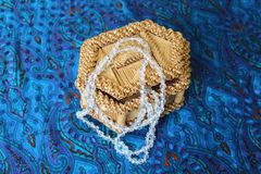Straw box for jewelry with beads. Straw box for jewelry with white beads. Yellow casket made of straw. Beads from rock crystal hang from it. Necklace decoration Royalty Free Stock Photography