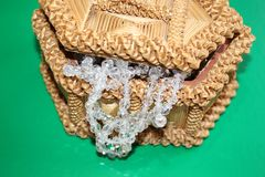 Straw box for jewelry with beads. Straw box for jewelry with white beads. Yellow casket made of straw. Beads from rock crystal hang from it. Necklace decoration Stock Image