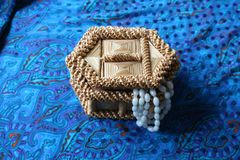 Straw box for jewelry with beads. Straw box for jewelry with white beads. Yellow casket made of straw. White beads hang from it. Necklace decoration, bijouterie Royalty Free Stock Photos