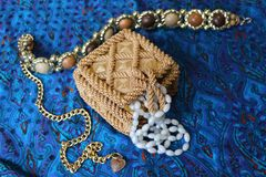 Straw box for jewelry with beads. Yellow casket made of straw. Beads from white precious stone hang from it. Next to the golden belt.  Necklace decoration Royalty Free Stock Photos