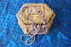Straw box for jewelry with beads. Straw box for jewelry with pink beads. Yellow casket made of straw. Beads from pink agate hang from it. Necklace decoration Royalty Free Stock Photography