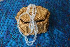 Straw box for jewelry with beads. Straw box for jewelry with white beads. Yellow casket made of straw. Beads from rock crystal hang from it. Necklace decoration Royalty Free Stock Images
