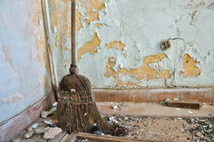 Straw broom on filthy floor Royalty Free Stock Photo